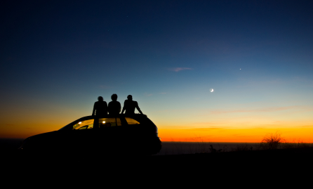 Two people sitting on a car during sunset